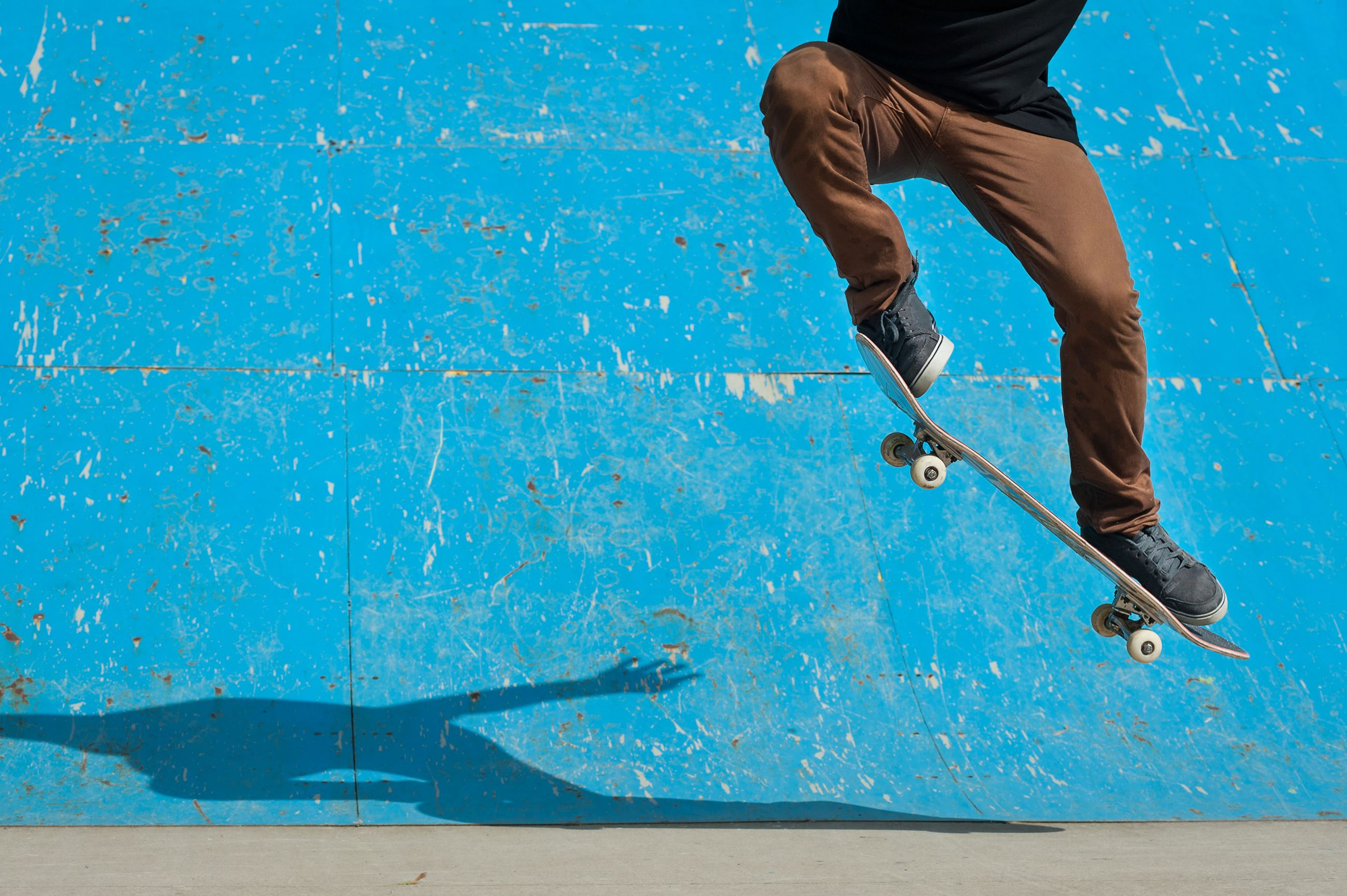 Guy on skateboard next to blue ramp with brown pants and black shirt doing an ollie